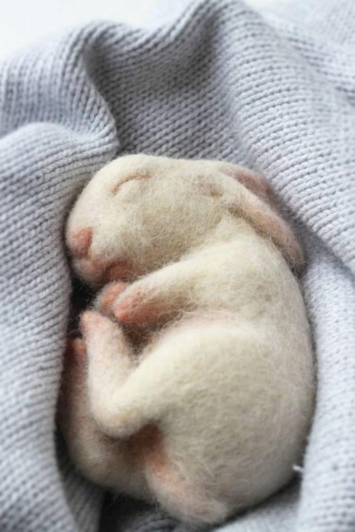 bricolage avec laine blanche, un petit lapin réalistique, lapin qui dort