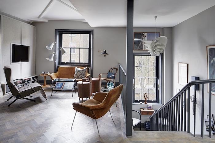amenagement salon mezzanine avec meubles style industriel, canapé cuir marron, fauteuil gris, chaise fauve, aprquet bois, table basse en metale t verre