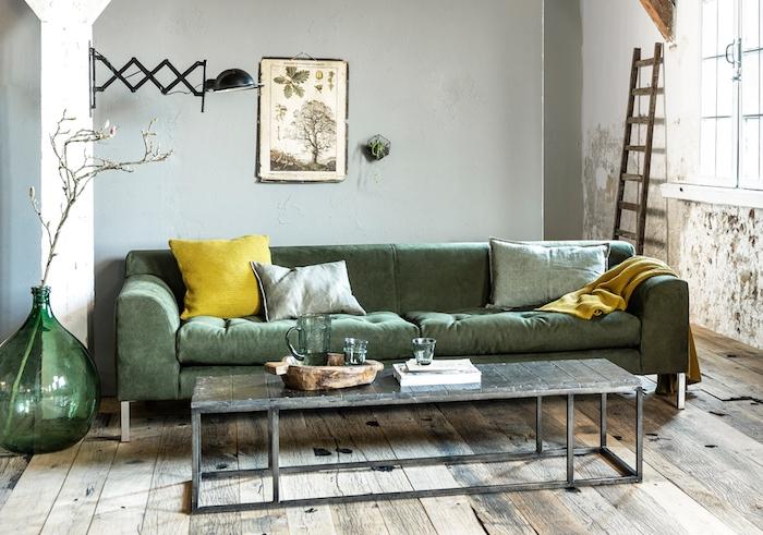 modele de petits salon industriel avec canapé vert coussins gris et jaune, table basse en bois et metal, parquet bois brut, echelle decorative, murs usés