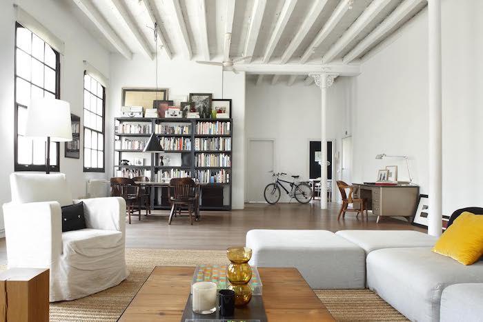 amenagement déco loft industriel avec canapé d angle blanc grisé, tapis beige, fauteuil blnc, table basse industrielle en bois et metal, ouverture sur espace travail