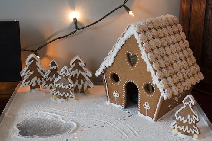 une maison en pain d épices avec décoration de glacage blanc et petits bonbons au chocolat blanc décorés de billes colorés, biscuits en forme de sapin, sucre glace en guise de neige