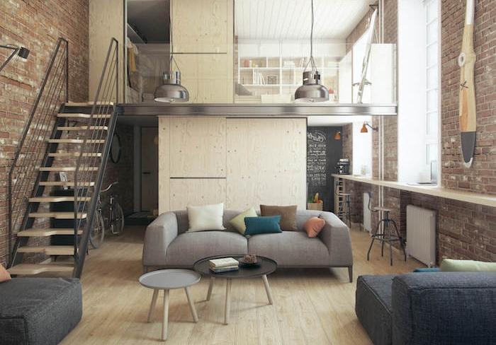 deco industrielle dans un salon avec canapé gris, tables basses rondes, parquet clair, escalier droit bois et metal, mur en briques, mezzanine