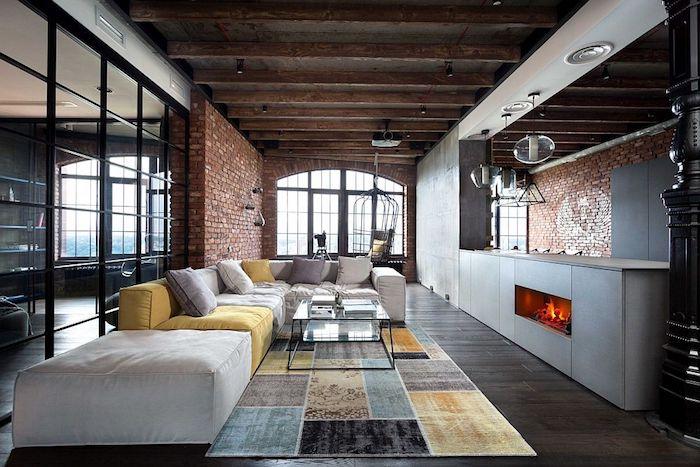 cuisine ouverte sur salon style industriel avec mur en briques, canapé gris et jaune, tapis à carrés bleu, jaune, gris et noir, poutres apparentes, suspensions industrielles