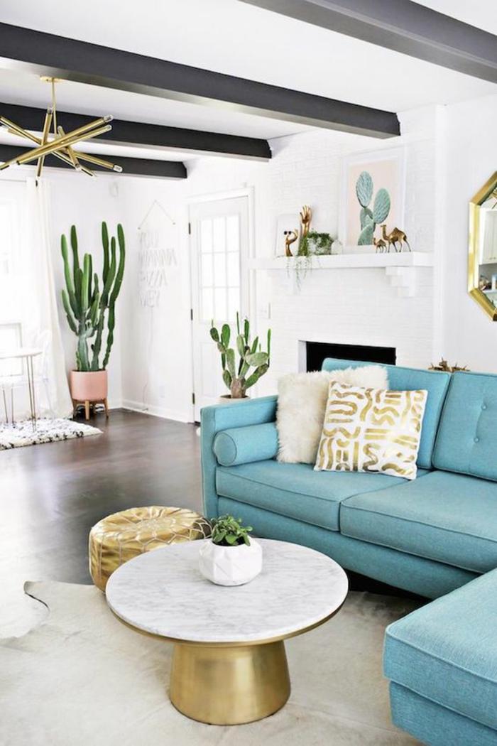 deco salon avec canapé modulaire angulaire en bleu turquoise, table ronde avec plan en blanc, tapis blanc imitation peau de vachette, des poutres noires rudes sur le plafond blanc en style rustique chic, miroir hexagonal au cadre doré