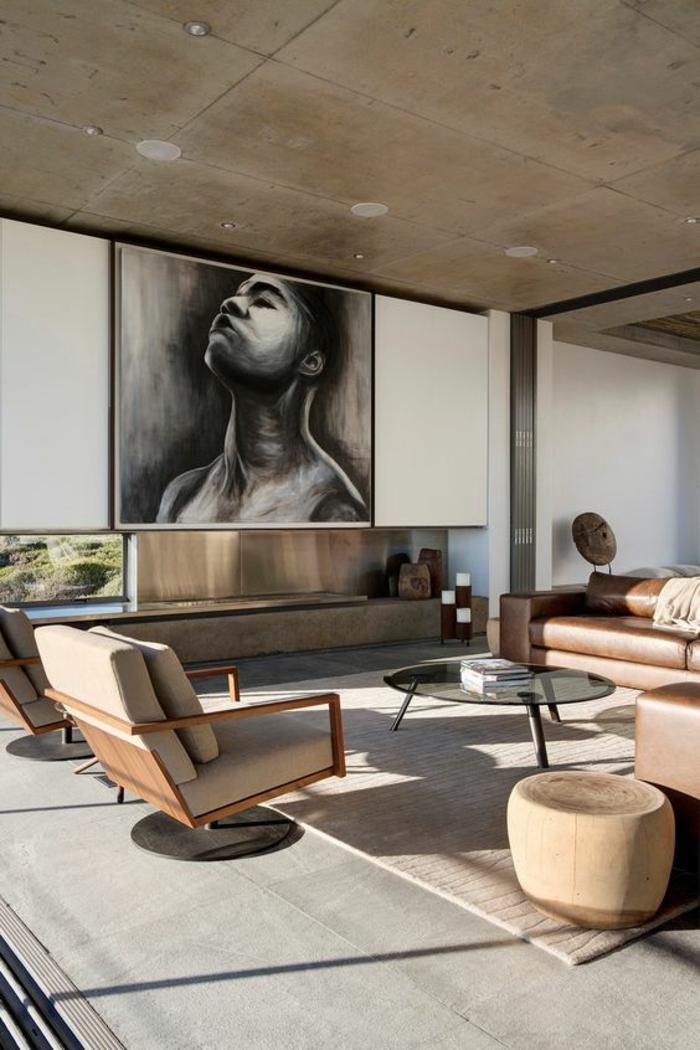 salon de luxe, deco salon avec cheminée moderne et dessin en noir et blanc sur le mur blanc, des meubles rétro, fauteuils en beige avec des grands coussins pour dossiers, tapis en gris clair, plafond en beige avec des luminaires insérés