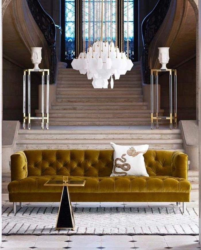 maison moderne de luxe, salon de luxe avec canapé long en jaune moutarde, tapis en blanc et noir, luminaire en blanc, deux tables pieds hauts des deux cotes de l'escalier avec vases blancs classiques