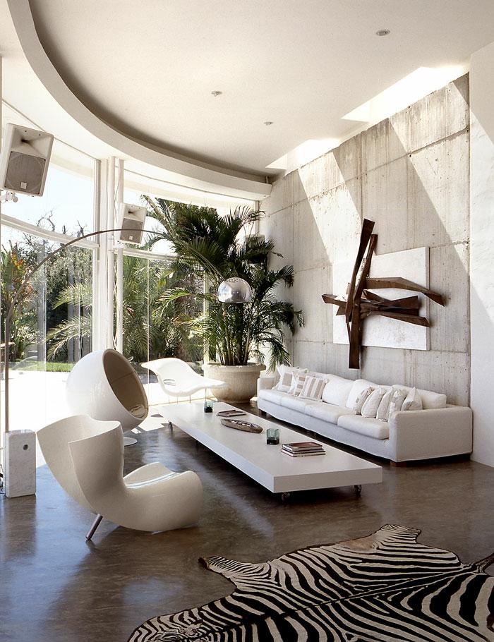 salon de luxe, maison moderne de luxe, avec canapé long rectangulaire blanc avec une multitude de coussins, table longue rectangulaire blanche en bois, fauteuil coque design en blanc, fauteuil rond design blanc
