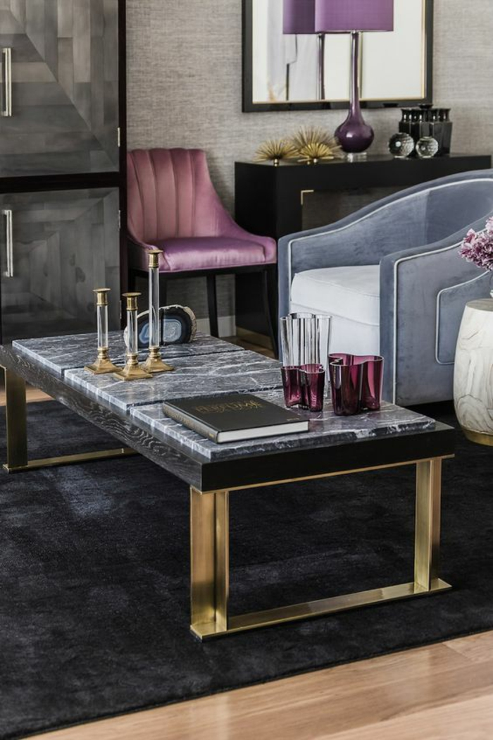 idée deco salon avec table rectangulaire en marbre noir et des pieds en métal doré, grand fauteuil bleu cuir, chaise en tissu rose et pieds en métal argent, ambiance luxe glamour, tapis noir, parquet beige laqué, meuble en noir