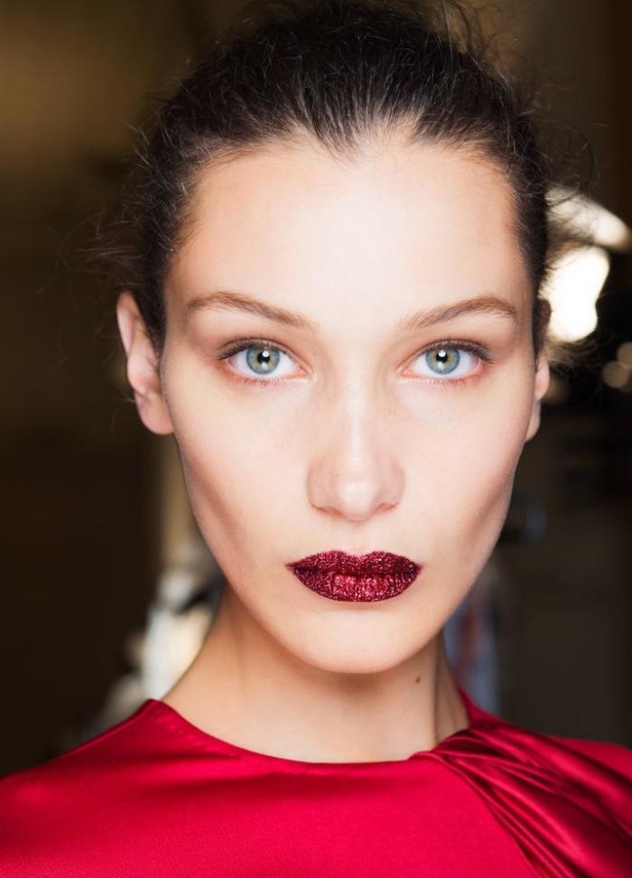 rouge a levre bordeau, femme aux cheveux attachés en chignon haut avec robe rouge et lèvres à paillettes