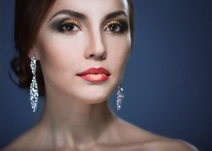 maquillage festif pour les fêtes de fin d'année en rouge à lèvres orange et yeux smoky avec fards à paupières dorés