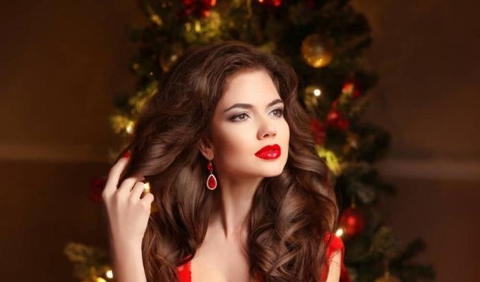 maquillage pour noel, brunette aux cheveux longs et bouclés avec robe et boucles d'oreilles rouges
