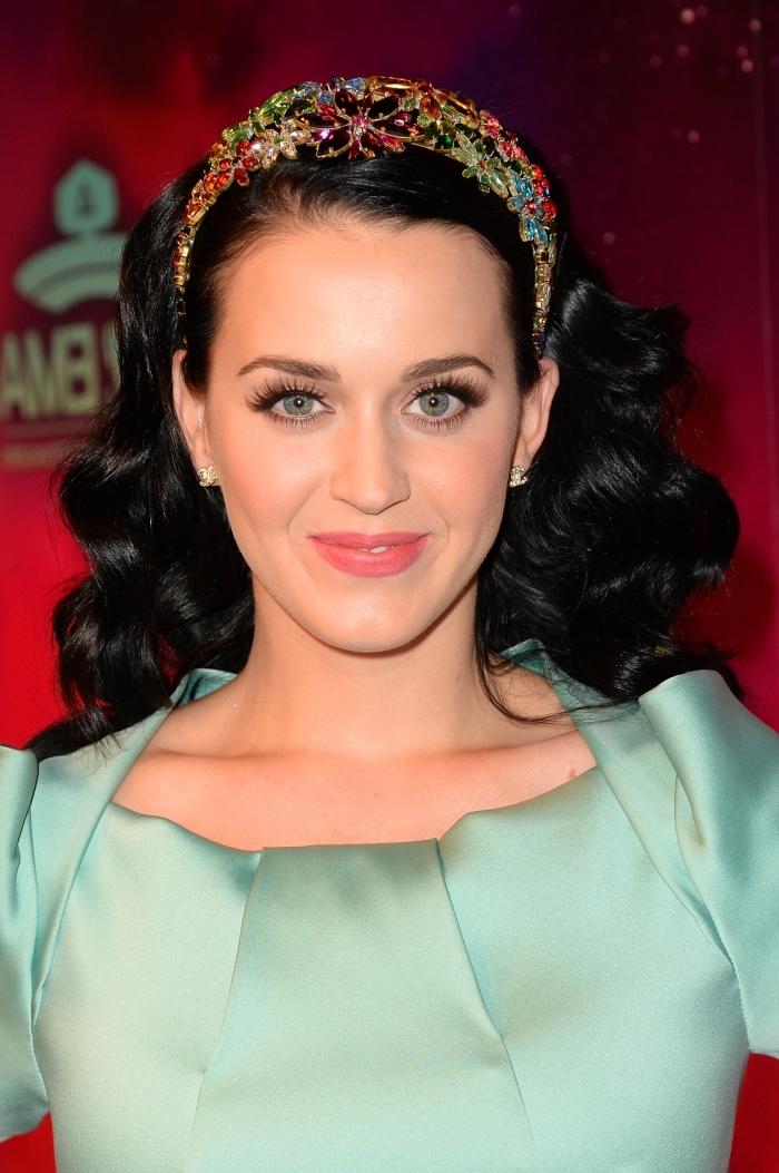 coiffure célébrité de Katy Perry aux cheveux longs et noirs bouclés avec diadème en cristaux et motifs floraux