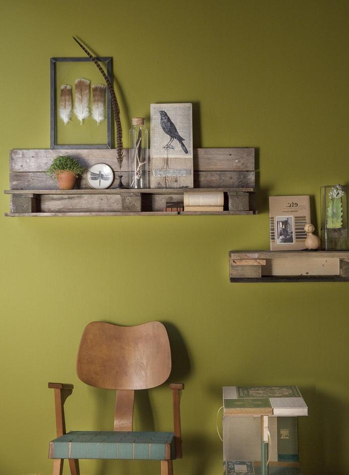des étagères murales en bois de palette en teinte foncée qui s'harmonise avec la peinture couleur ocre du mur
