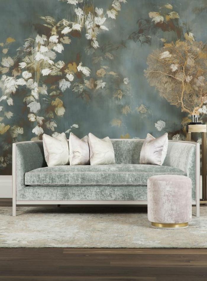 salon moderne de luxe, amenagement salon avec grand mur revêtu de tissu en bleu canard avec des fleurs en blanc, jaune et marron, style asiatique, canapé en velours en bleu pastel, tabouret rond en rose poudré, en style glamour, tapis blanc, parquet en marron clair et foncé