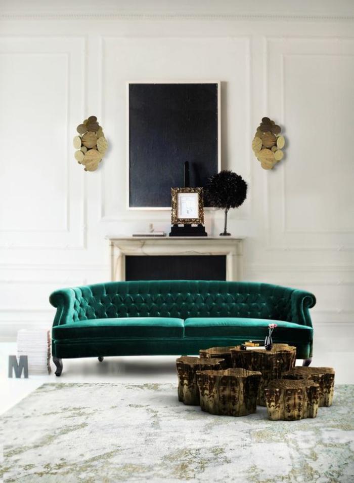salon de luxe avec canapé en velours vert émeraude, deux appliques murales art déco en métal doré, avec abat-jours en forme de multiples cercles