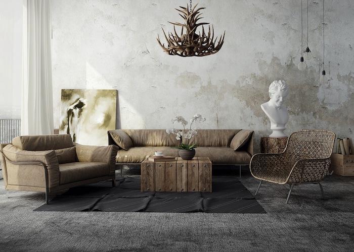 exemple de salon industriel artistique avec canapé et fauteuil gris, chaise originale, tapis gris, mur usé, lustre de bois de cerf, petite table basse en bois brut