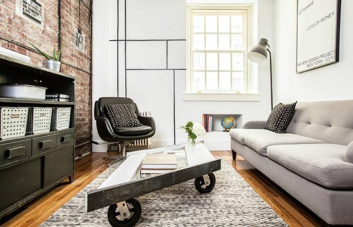 table basse industrielle en bois sur roulettes, tapis gris, parquet clair, canapé gris, meuble style industriel, mur en briques