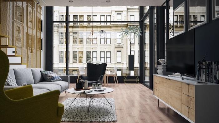 exemple de meuble tv industriel, parquet bois clair, tapis et canapé gris, table basse design, escalier avec grille jaune