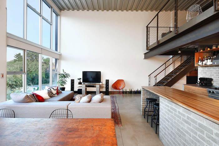 meubles tv industriel en bois et bloc en béton, sol en dalles effet béton, canapé d angle gris, tapis oriental, ouverture sur une cuisine, mezzanine