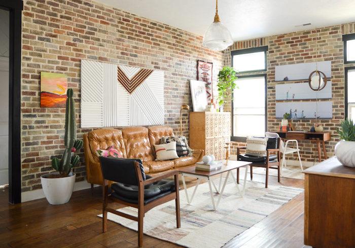 exemple de meubles style industriel dans un petit salon design, canapé en cuir marron, table basse en bois, chaises en bois et cuir, parquet marron, mur en briques
