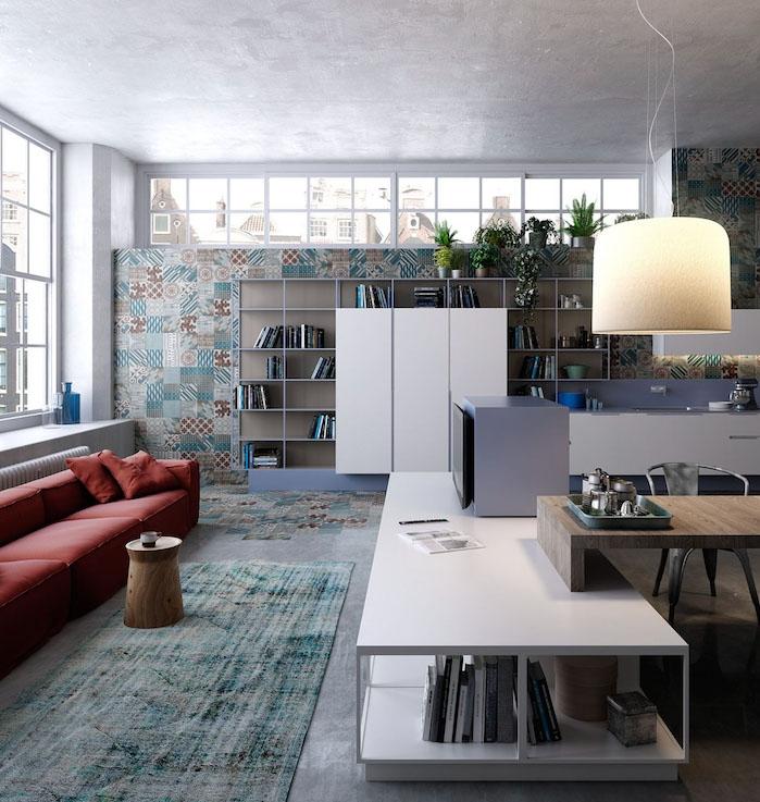 exemple de décoration industrielle salon avec canapé rouge, tapis gris et bleu, petite table bois ronde, bibliotheque moderne, mur habillé de mosaique originale, suspension design et ouverture sur salle à manger