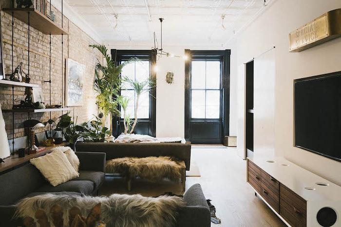 modele d etagere industrielle salon avec canapés gris, peaux animal, meuble tv industriel mur en briques, plantes