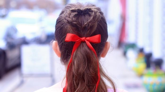 coiffure tresse chignon, cheveux longs de couleur marron attachés en queue de cheval et chignon en tresses avec ruban rouge