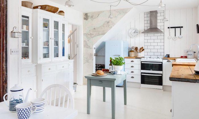 exempple cuisine angle blanche avec meuble bas blanc et plan de travail bois brut, sol blanc et petit comptoir bleu, pan de mur en carrelage blanc, aspirateur inox, vaisselier blanc avec vaisselle vintage dedans