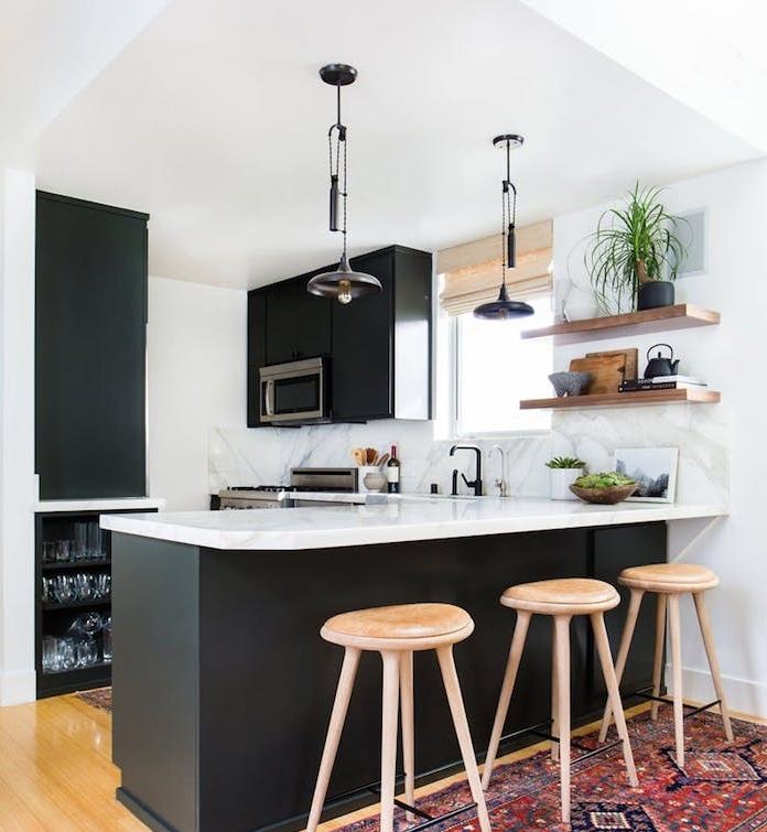 modele de cuisine en l noir mat avec plans de travail blanc, tapis oriental tabourets en bois, etageres en bois, suspensions industrielles