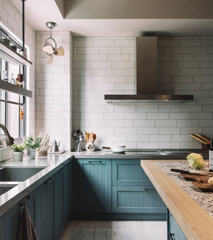 modele de cuisine amenagee avec meuble bas bleu et murs à effet briques, plan de travail gris, ilot central en bleu et plan de travail bois