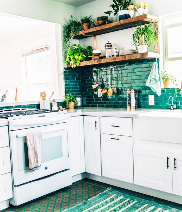 cuisine blanche et verte en l, avec meuble bas blanc, credence carrelage vert, etageres en bois rustiques, tapis vert et blanc, plantes vertes