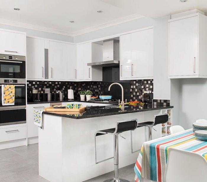 credence cuisine moderne en noir et gris, avec ilot central blanc avec plan de travail gris anthracite granite, sol carrelage gris