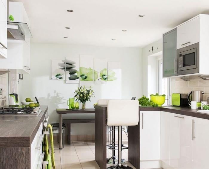 cuisines équiées avec des meubles cuisine blancs avec plan de travail en bois foncés, accessoires deco verts, carrelage sol beige, porte placard verre