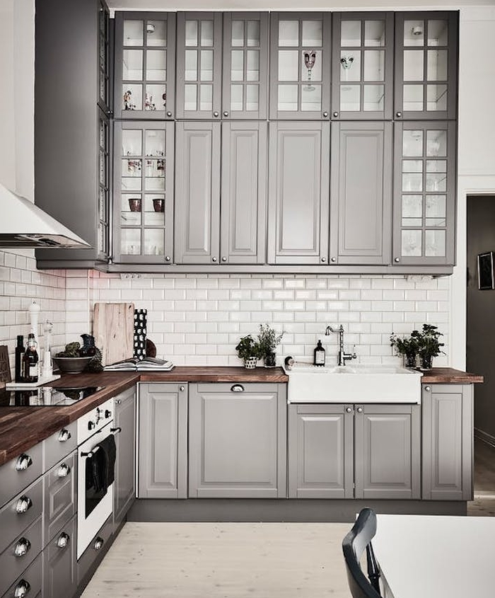 cuisine amenagee avec meubles hauts et bas gris, credence carrelage blanc, plan de travail bois foncé