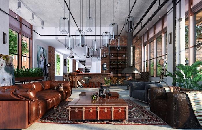 exemple deco industrielle salon avec canapé en cuir marron, table basse bois et plateau en verre, tapis oriental, suspensions originales, cuisine en briques