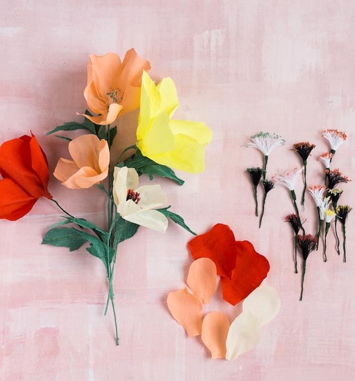 exemple de fleurs papier crepon avec des pétales colorées en orange, jaune et rouge et centre de fils noirs décorés de poudre colorée