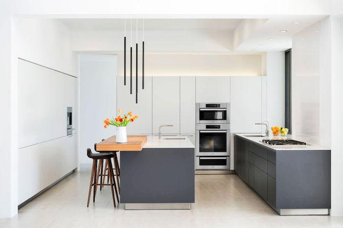 cuisine blanche et grise avec meuble cuisine bas et ilot central gris et plans de travail blancs, sol carrelage beige, armoire cuisine blanche, suspensions style industriel