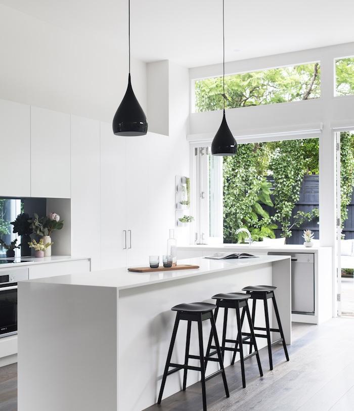 cuisine moderne blanche avec ilot central blanc entouré de tabourets noirs, sol parquet bois foncé, meuble cuisine blanc, suspensions noires