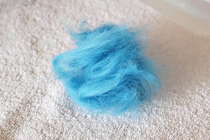 morceau de laine bleue pour former une boule ou un pompon avec de l'eau