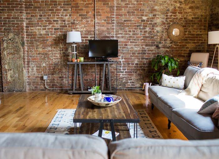 table basse industrielle en bois et metal noir, canapé gris, meuble tv industriel, mur en briques, parquet amrron