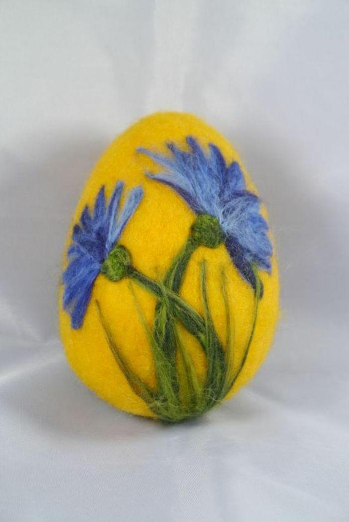 oeuf de Pâques, un oeuf jaune avec des fleurs bleues feutrées sur la base