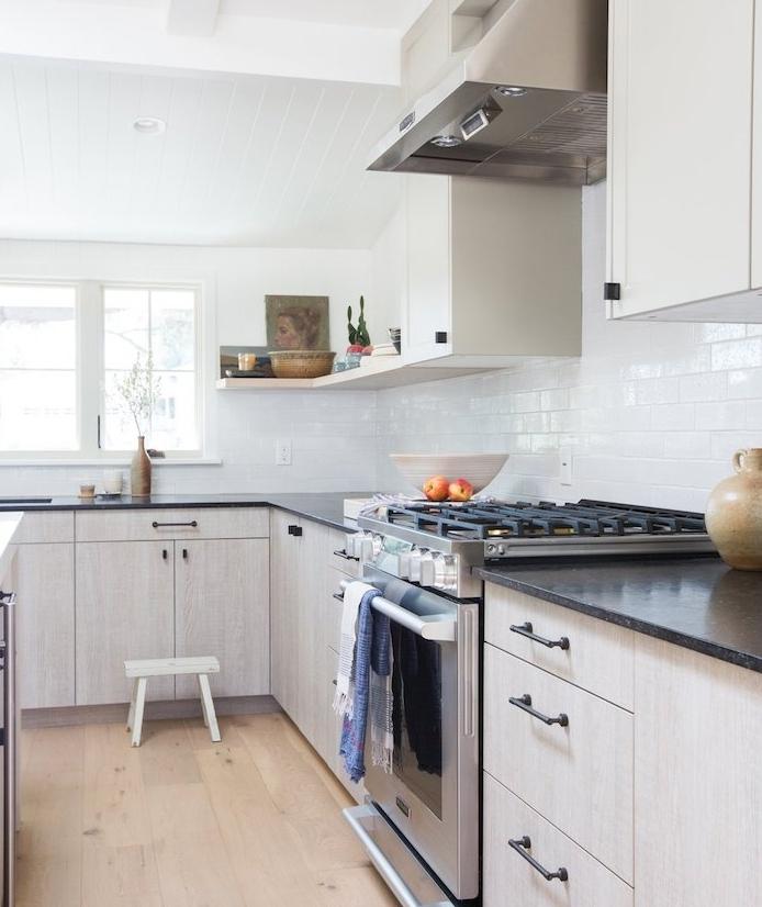 petite cuisine équipée avec meuble bas bois clair et plan de travail noire, meuble hait blanc, aspirateur inox, parquet clair