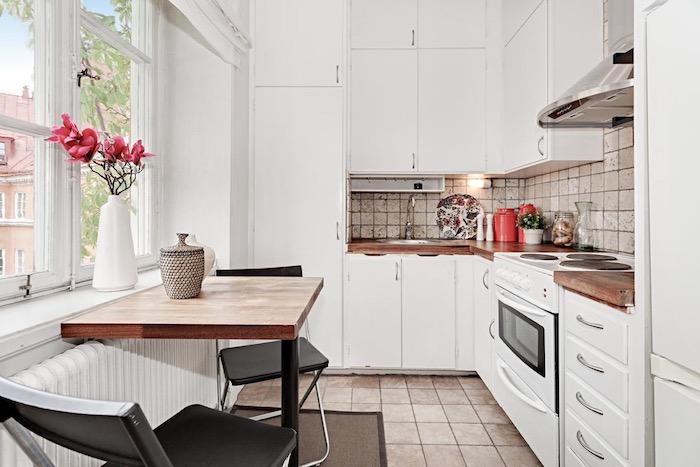 modele de cuisine blanche avec meubles hauts et meubles bas blancs, carrelage sol et credence cuisine beige, plan de travail bois marron, table et chaises noires