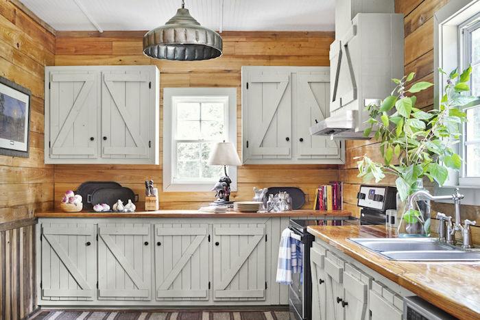 modele de cuisine bois et blanc avec revetement mural bois clair, meubles hauts et bas à portes placard blanc vintage, tapis gris et blanc, aspirateur inox