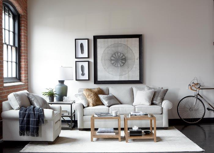 déco loft industriel avec canapé et fauteuil blanc cassé, table basses en verre et bois, tapis blanc, parquet marron, mur en briques