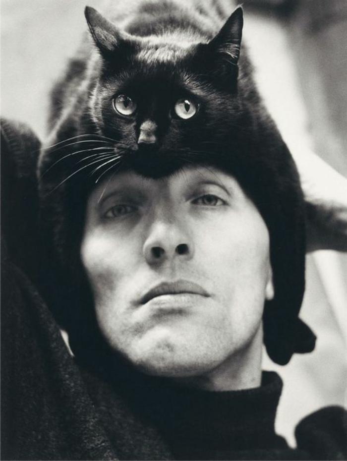 f850caae1d5aa image noir et blanc, un homme avec un chat noir aux yeux verts sur sa