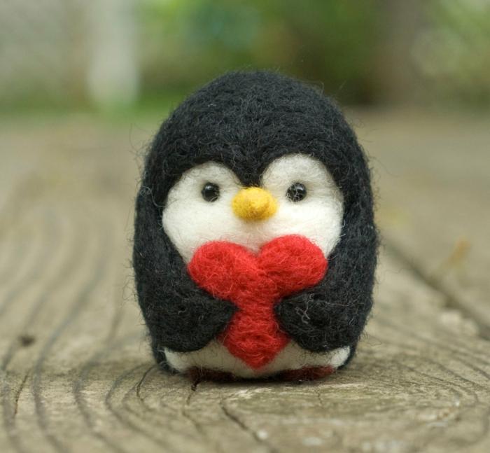 pingouin qui porte un grand coeur rouge fait en laine, un travail professionnel