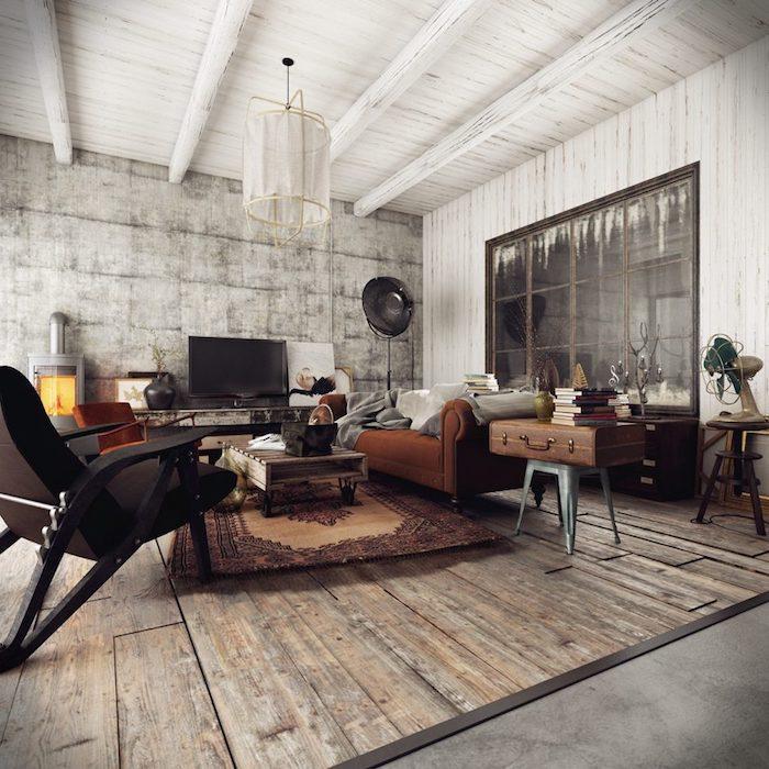 déco loft industriel dans un salon avec canapé marron, table basse en palette à roulettes, sol en bois, suspension blanche, deco malle vintage et vieux bouquins, poutres blanches