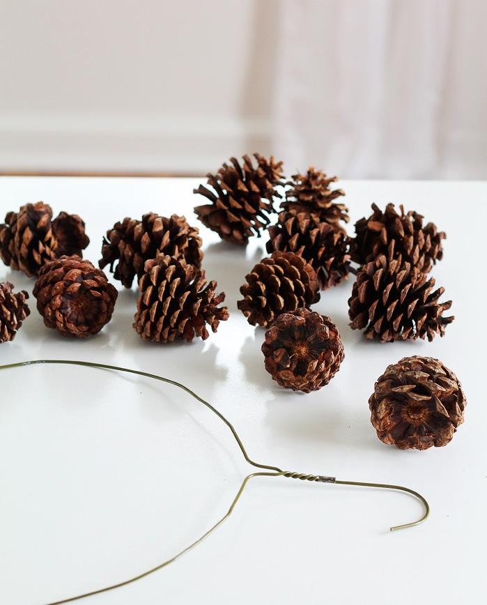 un bricolage de noel original avec des matériaux naturels, une couronne de noël réalisée avec des pommes de pin et un cintre métallique