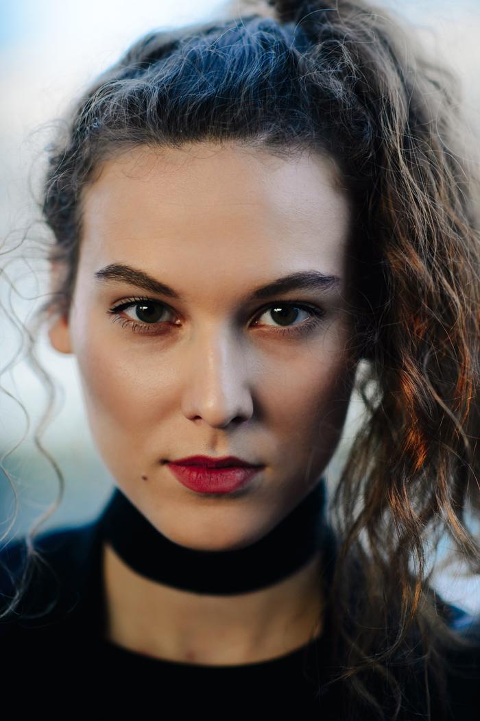 une coiffure femme facile à réaliser pour affiner le visage rond, une queue-de-cheval haute sur le côté inspirée des années 90 réalisés sur des cheveux ondulés